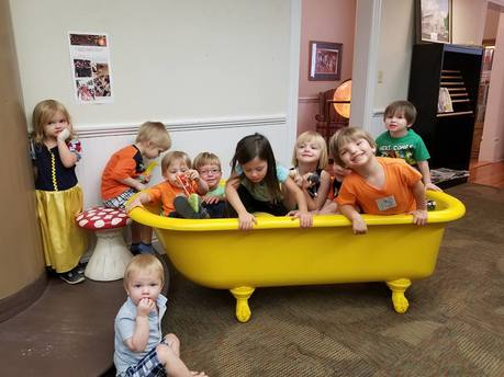 Photo of preschool children setting in yellow reading tub that is filled stuffed animals.